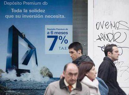 Viandantes ante los carteles de una entidad financiera con ofertas para remunerar el ahorro.