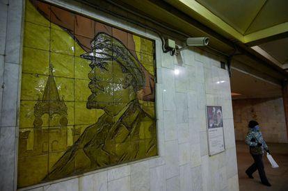 Una mujer pasa cerca de una cámara de seguridad situada junto a un mosaico de Lenin en una estación de metro de Moscú.