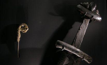 Alfiler con cabeza de dragón que sugiere los adornos de las proas de los barcos y espada vikinga, de la exposición.