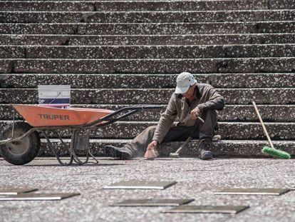 Un trabajador hace tareas de limpieza en la escalinata del Auditorio Nacional de México.