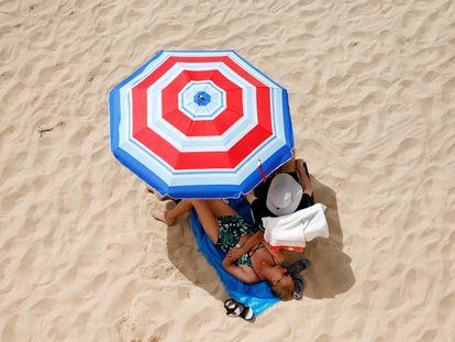 Dos de turistas disfrutan del sol y el mar en la playa de Levante de Benidorm, este viernes.
