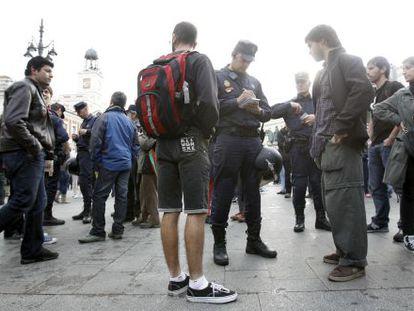 Los policías piden la documentación a uno de los concentrados en Sol.