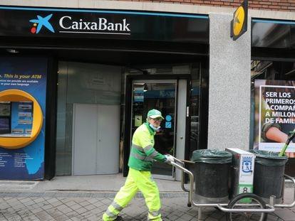 Un operario de limpieza pasa por delante de una oficina de CaixaBank, en Madrid, el 22 de abril.