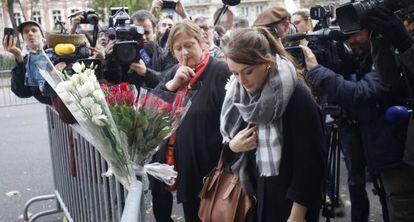Personas depositan flores cerca de la sala Bataclan.