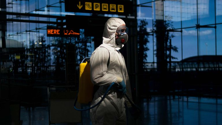 A member of the Military Emergencies Unit (UME) carries out a general disinfection at Malaga airport on March 16, 2020. - Spain has registered nearly 1,000 new COVID-19 infections over the past 24 hours, raising the total number of cases to 8,744. In order to rein in the virus, Spain has declared a state of alert, shutting all but essential services and ordering its population of 46 million people to stay at home. People are only authorised to go out to buy food or medicine, to go to work or to get medical treatment. (Photo by JORGE GUERRERO / AFP)