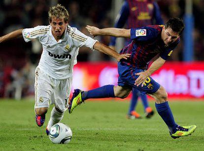 Coentrão se lleva un balón ante Messi durante el partido de vuelta de la final de la Supercopa.