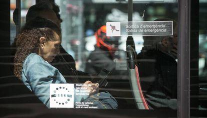 Una pasajera utiliza su teléfono móvil en un autobús público de Barcelona