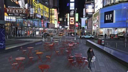 Una mujer camina por un Times Square casi vacío.