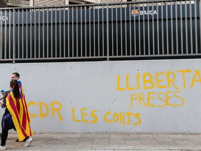 """Dos manifestantes independentistas caminan este miércoles por delante del Camp Nou, en Barcelona,ante una pintada que reza """"libertad presos cdr Les Corts""""."""