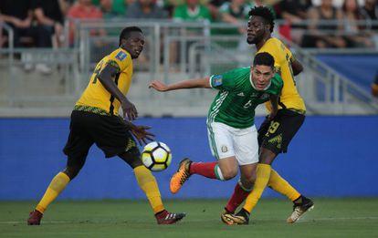 Álvarez pasa en medio de los defensores de Jamaica.