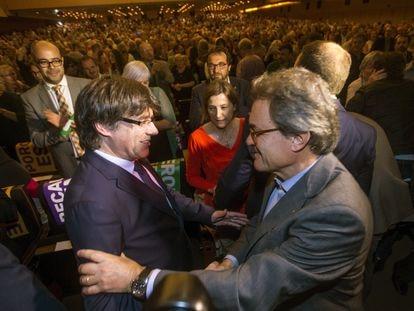 Carles Puigdemont y Artur Mas se saludan, en presencia de Carme Forcadell, durante el acto central del Pacto Nacional por el Referéndum.