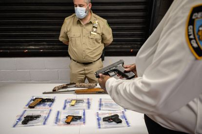 A NYPD officer holds a handgun during a voluntary surrender of weapons by citizens in Brooklyn on May 22.