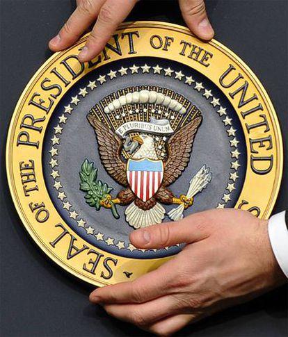 Un miembro del equipo de Gobierno coloca la señal presidencial antes de que Obama ofrezca la conferencia en la que se celebró la ratificación del tratado de desarme nuclear con Rusia.