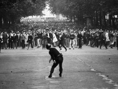 En el Bulevar Saint Germain de París un policía devueve un adoquín a los estudiantes durante el Mayo del 68 francés.