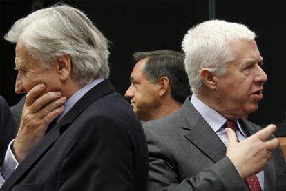 Jean-Claude Trichet, a la izquierda, de espaldas al ministro de Finanzas portugués, Fernando Teixeira dos Santos, ayer en Bruselas.