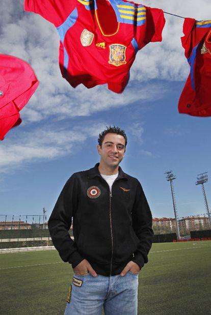 Xavi, en la Ciudad Deportiva del Barça, con varias camisetas que ha utilizado con España.