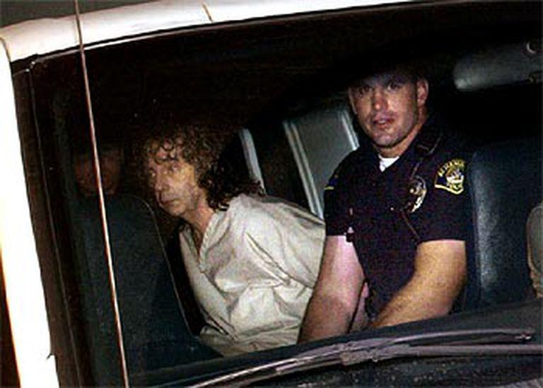 Phil Spector, acompañado de un policía de Los Ángeles tras su detención. A la izquierda, la actriz Lana Clarkson.