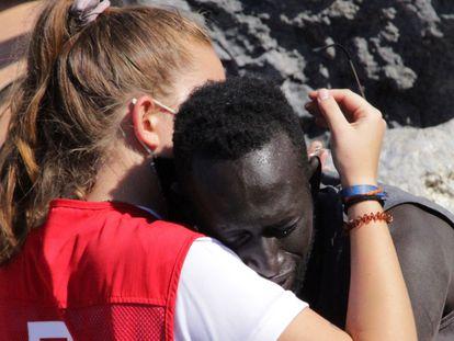 Abdou, senegalés de 27 años, se abraza a la voluntaria de la Cruz Roja Luna Reyes, el pasado martes en la playa del Tarajal (Ceuta).