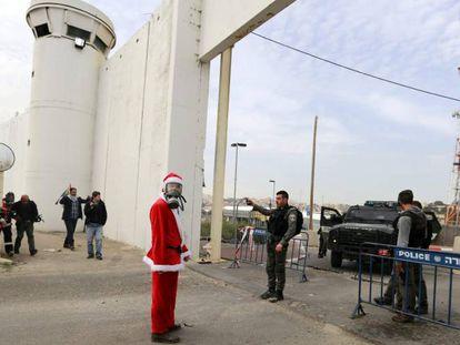 Un manifestante disfrazado de Papá Noel, ante el muro de separación en Belén.
