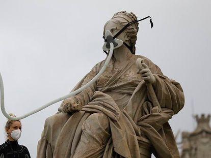 Activistas de Greenpeace colocan una mascarilla a la Cibeles.