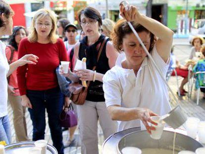 Un grupo de viandantes prueba la horchata de la calle Alcalá.