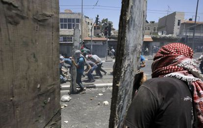 Jóvenes palestinos lanzan piedras a las fuerzas de seguridad israelíes en los disturbios tras el funeral del joven palestino asesinado.