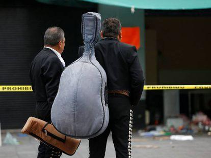 Dos mariachis observan el lugar de la plaza Garibaldi donde la semana pasada fueron asesinadas cinco personas
