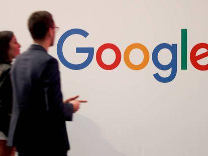 Dos personas pasan junto al logotipo de Google en París.