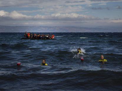 Llegada de botes atestados de refugiados a la isla de Lesbos y, en primer plano, tres socorristas para ayudarlos.