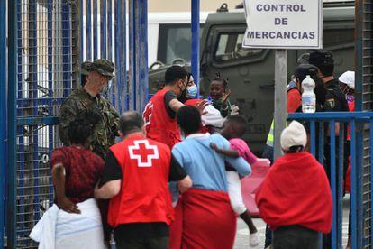La Cruz Roja ayuda a varias mujeres y a sus hijos a su llegada a Ceuta, el miércoles.
