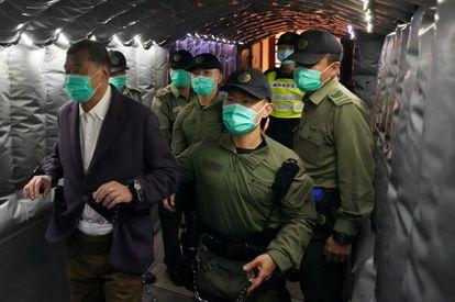 El magnate de prensa Jimmy Lai abandona el Tribunal Supremo de Hong Kong escoltado por varios agentes que lo llevan de nuevo a prisión este jueves en Hong Kong.