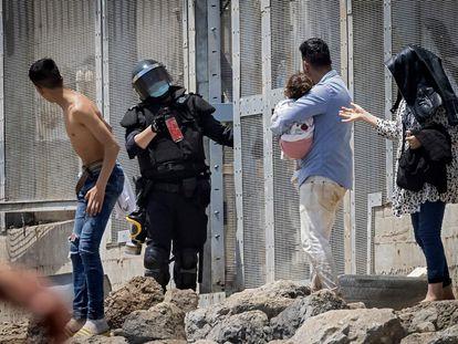 La policía española intenta dispersar a los migrantes en la frontera entre Marruecos y el enclave español de Ceuta, el martes.