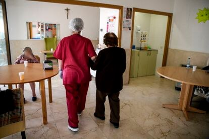 Una empleada ayuda a una mujer a sentarse en la residencia de ancianos Santa María de Montecarmelo en Madrid.