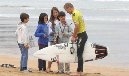Cuatro niños piden un autógrafo a uno de los surfistas que participan en la prueba.