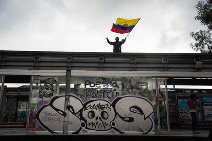 Un manifestante con la bandera de Colombia protesta sobre una estación de bus en la ciudad de Bogotá.