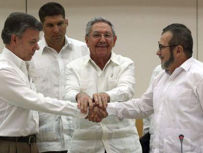 Juan Manuel Santos y Rodrigo Londoño, 'Timochenko', se dan la mano en La Habana junto a Raúl Castro, en septiembre de 2019.