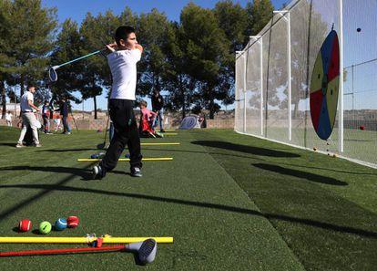 Un niño juega al golf en Brea.