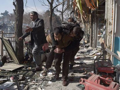 Un voluntario carga con un cuerpo tras un ataque talibán en Kabul en enero de 2018 en el que murieron 17 personas.