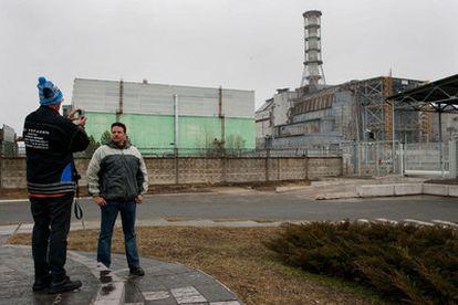 Turistas se hacen fotos frente a los restos del reactor número 4 de Chernobil.