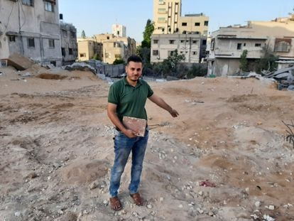 El librero Shaban Eslim señala el lugar donde se encontraba su librería, destruida por los bombardeos israelíes, con un Corán rescatado de entre los escombros, el día 9 de septiembre en Gaza.