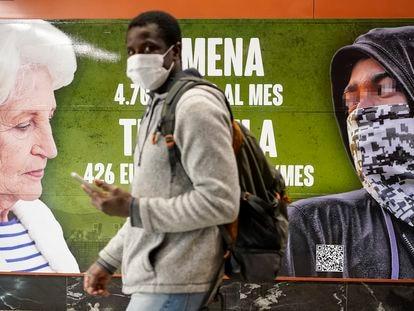 Un hombre pasa ante el cartel contra los menores extranjeros colocado por Vox en una estación de tren de Madrid.