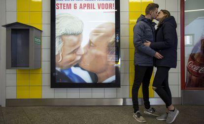 Una pareja se besa junto a un poster con una caricatura en la que el político holandés Geert Wilders besa al presidente ruso Valdímir Putin en el metro de Ámsterdam.