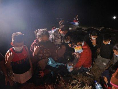 Familias ecuatorianas rezan después de cruzar el río Grande desde México, el 14 de abril en Roma, Texas.