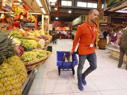 Un empleado recoge pedidos de Amazon en el mercado de La Paz en Madrid.
