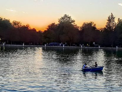 Varias personas pasean en una barca por El Retiro.