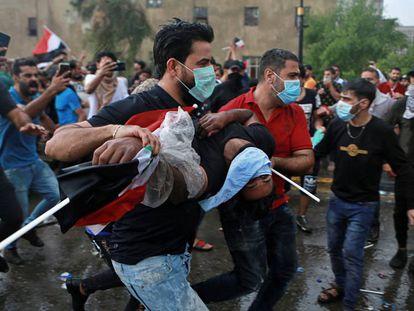 Dos hombres transportan a un herido en medio de una protesta en Bagdad, este viernes. En vídeo, imagenes de las protestas.