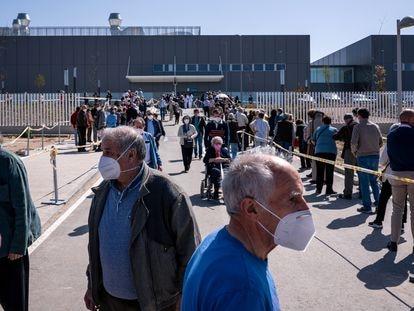 Decenas de personas hacen cola para recibir la vacuna en el Hospital Isabel Zendal durante la Semana Santa.