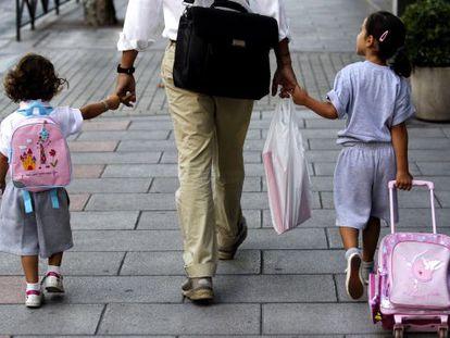 Un padre lleva a sus hijas al colegio en Madrid.