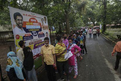 Un grupo de personas hace cola para vacunarse contra la covid-19 en la puerta de un centro de vacunación en Mumbai, India, el martes 17 de agosto de 2021.