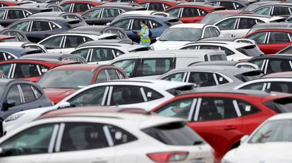 Una trabajadora de Ford camina, en mayo del año pasado, entre automóviles aparcados en el exterior de la planta en Almussafes (Valencia), listos para ser enviados a los concesionarios.